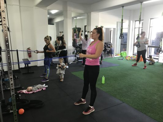 fitness women doing postnatal exercise with bubs in ladies gym